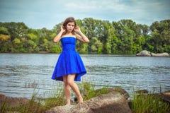 Portret die van mooie jonge donkerbruine vrouw, elegante blauwe kleding dragen Royalty-vrije Stock Foto