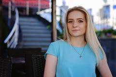Portret die van mooie jonge vrouw met blond haar en lange wimpers, in een koffie zitten stock afbeelding