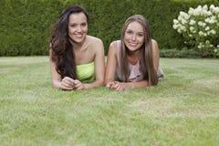 Portret die van mooie jonge vrouwen met lang haar in park liggen Royalty-vrije Stock Foto