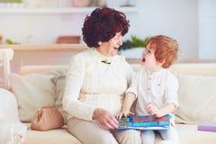 portret die van mooie rijpe vrouw 80 jaar oude dame met haar groot-kleinzoon thuis, onderwijsboek samen lezen stock fotografie