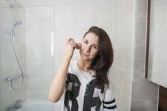 Portret die van mooie vrouw make-up in badkamers toepassen Royalty-vrije Stock Foto