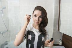 Portret die van mooie vrouw mascara in badkamers toepassen Stock Afbeeldingen