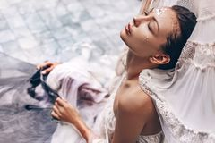 Portret die van mooie vrouw in water met stof liggen Manier stock fotografie