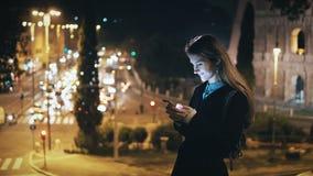 Portret die van mooie vrouw zich dichtbij de verkeersweg en Colosseum bevinden in Rome, Italië en het gebruiken van smartphone Royalty-vrije Stock Afbeelding