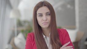 Portret die van onderneemster zich in een licht comfortabel bureau bevinden die de camera bekijken Succesvol zeker meisje in stock footage