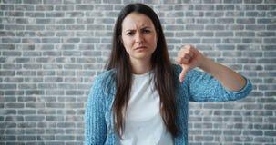 Portret die van ongelukkig meisje duim-neer op bakstenen muurachtergrond tonen stock videobeelden