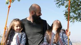 Portret die van papa met dochters op een schommeling onder een boom slingeren stock video