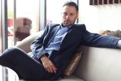 Portret die van positieve jonge zakenmanzitting in een modern collectief milieu, de camera bekijken stock afbeelding