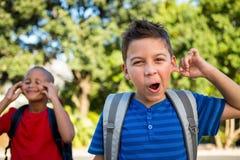 Portret die van schooljongen een gezicht maken stock foto