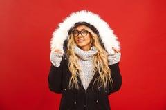 Portret die van tevreden vrouw, een warm de winterjasje met kap het dragen, heeft blije uitdrukking, voelt warm en comfortabel royalty-vrije stock foto