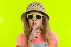 Portret die van tienermeisje in zonnebril en strohoed met een wijsvinger dichtbij de lippen, stilteteken, geheim geel gebaar tone royalty-vrije stock afbeelding