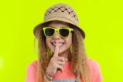 Portret die van tienermeisje in zonnebril en strohoed met een wijsvinger dichtbij de lippen, stilteteken, geheim geel gebaar tone royalty-vrije stock foto