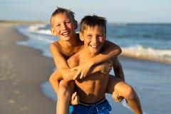 Portret die van twee gelukkige jonge geitjes op het strand op de zomervacati spelen royalty-vrije stock afbeeldingen