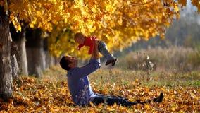 Portret die van vader op babykind opheffen in mooie de herfstaard stock footage
