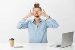 Portret die van verbaasde knappe vrouwelijke ondernemer in bureau, ogen behandelen met palmen en impatiently wachten voor royalty-vrije stock fotografie