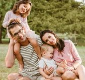 Portret die van vrolijke familie in het park rusten stock afbeeldingen