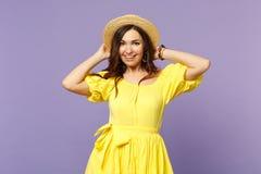Portret die van die vrolijke jonge vrouw die in gele kleding handen op de zomerhoed zetten, camera kijken op pastelkleurviooltje  stock foto's