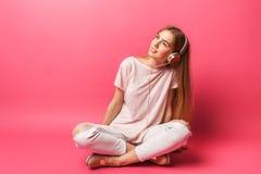Portret die van vrolijke mooie meisjeszitting op vloer en weg het kijken, aan muziek in oortelefoons, op roze backgroun luisteren royalty-vrije stock fotografie