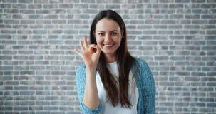 Portret die van vrolijke vrouw het O.K. handgebaar glimlachen tonen die camera bekijken stock videobeelden