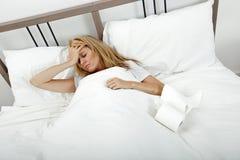 Portret die van vrouw aan koude en hoofdpijn in bed lijden Stock Foto's