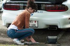 Portret die van vrouw de slechte uitstekende Amerikaanse die auto van de meisjesnummerplaat het veranderen van Pontiac-merk bij p royalty-vrije stock afbeelding
