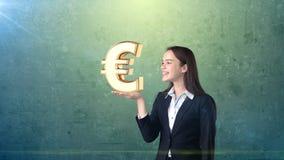 Portret die van vrouw gouden euro teken op de open handpalm houden, over geïsoleerde studioachtergrond Bedrijfs concept Stock Foto
