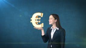 Portret die van vrouw gouden euro teken op de open handpalm houden, over geïsoleerde studioachtergrond Bedrijfs concept Stock Foto's