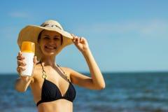 Portret die van vrouw skincare met zonneschermlotion bij strand nemen stock afbeelding