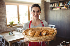 Portret die van vrouwelijke bakker een mand van broodbroden houden royalty-vrije stock fotografie