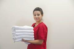 Portret die van vrouwelijke huishoudster schone witte handdoeken houden tegen grijze achtergrond Stock Afbeeldingen