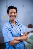 Portret die van vrouwelijke verpleegster zich in afdeling bevinden royalty-vrije stock afbeelding