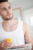 Portret dobrego przyglądającego mężczyzna pije sok pomarańczowy podczas gdy readi Fotografia Royalty Free