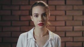 Portret doen schrikken vrouw met geopende mond van schok op bakstenen muurachtergrond stock video