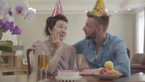 Portret dojrzała kobieta i dorosłego wnuk opowiada siedzieć przy stołem z urodzinową nakrętką na ich głowach Na stole zbiory wideo