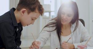 Portret dojrzała kobieta wydaje czas z jej synem maluje wpólnie dla szkolnego projekta, bardzo atrakcyjni ludzie wewnątrz zbiory wideo