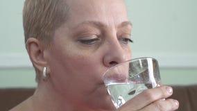 Portret dojrzała kobieta z krótkim blondynem który woda pitna od szkła zbiory wideo