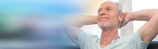 Portret dojrzałego mężczyzna słuchająca muzyka z słuchawkami, lekki skutek Fotografia Stock