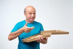 Portret dojrzały europejski mężczyzna je plasterek pizza W jego rękach trzyma pudełko jedzenie Pracowniany krótkopęd obrazy stock