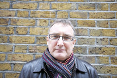 Portret dojrzały mężczyzna jest ubranym szkła z szalikiem przeciw ścianie Obraz Stock