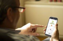 Portret dojrzały mężczyzna tłumaczy tekst w telefonie komórkowym Obrazy Stock