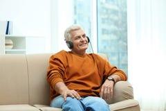 Portret dojrzały mężczyzna z hełmofonami na kanapie zdjęcie royalty free