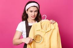 Portret dokuczająca wzburzona kobieta stnading z żółtą koszula na wieszaku, trzymający loupe, robi plamie duża, denerwującego z b obraz stock