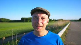 Portret dorosła uśmiechnięta mężczyzna pozycja z łąką przy tłem Beztroski facet w kapeluszowy patrzeć w kamerę z zwężający się zbiory