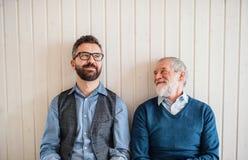 Portret dorosły modnisia syn i starszy ojca obsiadanie na podłodze indoors w domu zdjęcie royalty free