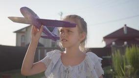 Portret dosyć śliczna mała dziewczynka bawić się z małym samolotem w górę Dziecko wydaje czas outdoors w zdjęcie wideo