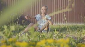 Portret dosyć śliczna mała dziewczynka wszczyna małego płaskiego obsiadanie na trawie pod ogrodzeniem Dziecko wydatki zbiory