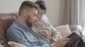 Portret dosyć dojrzała kobieta i dorosłego wnuk siedzi w domu oglądający stare fotografie w dużym albumu fotograficznym rodzina zbiory wideo