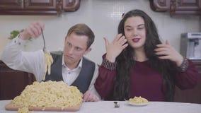 Portret dosyć ufna dosyć tłuściuchna kobieta i chuderlawy mężczyzna w kuchni przy stołem przed mały i dużym zbiory