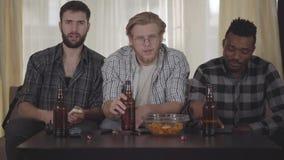 Portret drie gelukkige vrienden die bij huis op cauch zitten, kijkend TV, het drinken bier met spaanders, die een videogesprek he stock videobeelden