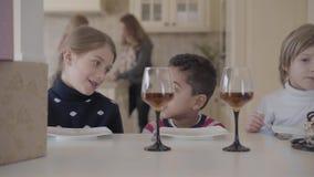 Portret drie grappige jonge geitjes die bij de lijst met kleine cake en wijnglazen met sap zitten Twee Kaukasische meisjes en stock video